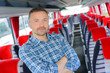 Portrait of man stood in aisle of empty bus