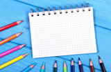 Colorful crayons and notepad on boards, school accessories, copy space for text - 212405365