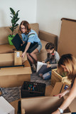 Family unpacking cardboard boxes at new home - 212410759