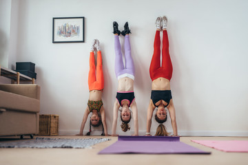 Females doing handstand pose near wall. Mother and daughters exercising at home, sport, family © undrey