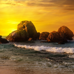 Sea landscape with rocky island and the sunrise.