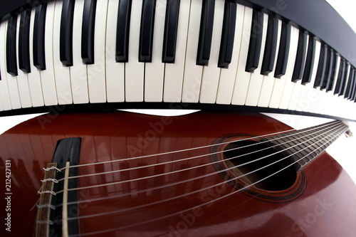 piano keys and classical guitar close up on white background - 212427131