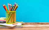 Holder with colored pencils on  school supplies on table against blue background. Space for text. - 212431154
