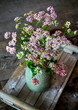 A bouquet in a vase of summer wild flowers on a wooden table, in rustic style.