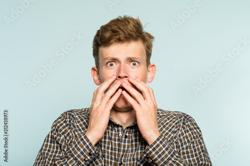 scared shocked terrified frightened startled man clutching hands to his face. portrait of a young guy on light background. emotion facial expression. feelings and people reaction concept.