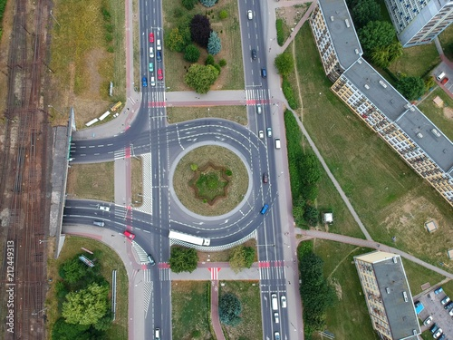 Aerial view on roundabout intersection with cars traffic and railroad