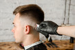 Barber does hair cut young guy on a brick wall background.