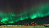 Aurora boreale sulle casette rosse