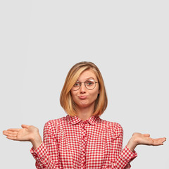 Puzzled female student feels awkward and hesitant, doesn`t know material for exam, wears spectacles and checkered blouse, poses against white background with copy space upwards for your text