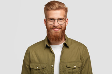 Horizontal shot of attractive red haired male has gentle smile, feels joy after successful working day, wears spectacles and fashionable shirt, has ginger long beard and trendy hairdo, stands indoor