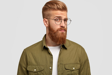 Sideways shot of handsome bearded ginger male looks with mysterious expression, wears spectacles and green shirt, stands against white background. Stylish red haired young man wonders something
