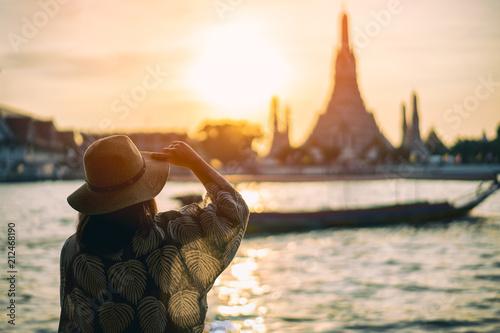 Leinwanddruck Bild Young woman traveler traveling into Wat Arun Ratchawararam Ratchawaramahawihan Temple in bangkok, Thailand at sunset