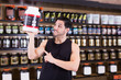 Positive athletic man seller  holding big pot of sport supplements i