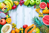 Assortment of tropical fruits with palm leaves and exotic flowers - 212474184