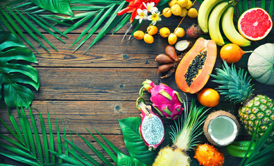 Assortment of tropical fruits with leaves of palm trees and exotic plants on dark wooden background © Alexander Raths