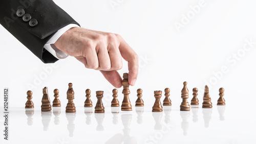 Fototapeta Businessman playing chess reaching dark king piece at white table