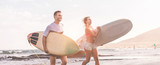 Happy surfers running with surf boards on the beach - 212485323