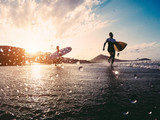 Silhouette of happy surfers running with surf boards on the beach - 212486317