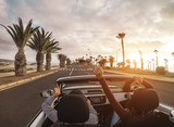 Happy people having fun in convertible car in summer vacation - Young couple laughing on cabrio auto outdoor - Travel, youth lifestyle, holidays and wanderlust concept - 212486592