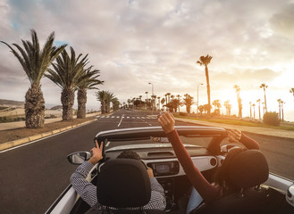 Happy people having fun in convertible car in summer vacation - Young couple laughing on cabrio auto outdoor - Travel, youth lifestyle, holidays and wanderlust concept