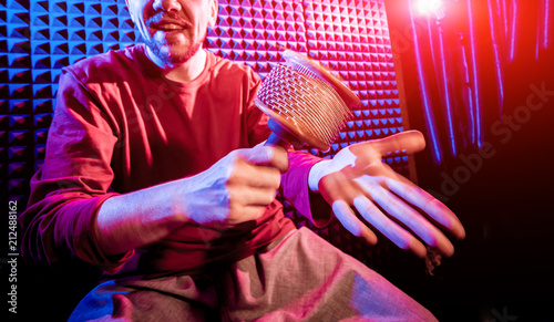 Fotobehang Muziek Young man playing on maracas in sound recording studio.