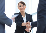 Businesswoman shaking hands with a businssman during a meeting - 212492784