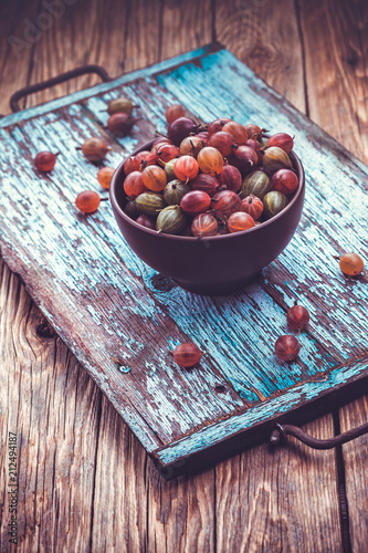 Foto Murales old wooden tray with gooseberry on the table