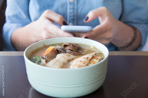 food, technology, eating and people concept - woman sitting at cafe table with smartphone and bowl of vegetable chicken soup