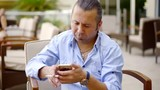 Portrait of adult elegant man using smartphone and smoking on outdoor restaurant terrace in summer. - 212501397