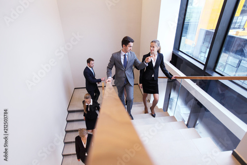 Wall mural Group of business people walking at stairs