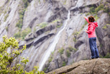 Woman on mountain rock enjoying beautiful view