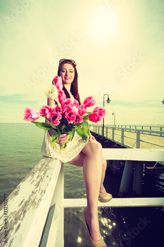 Woman holding bouquet of flowers sitting on pier - 212510199
