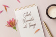 Leinwanddruck Bild - collect moments, not things - motivational / inspirational quote written on a notepad, top view of a minimalist desk with flower, petals golden pen and candles