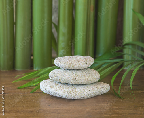 Fotobehang Zen Relaxation symbol/Pyramid of white calcareous stones and green bamboo trunks on wooden background
