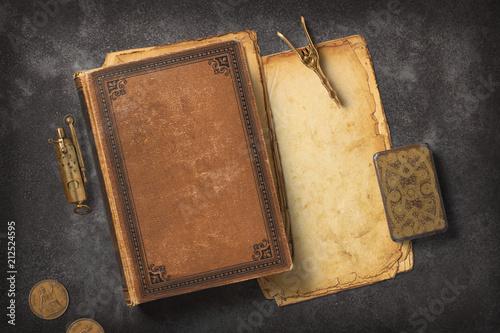 Leinwanddruck Bild Steampunk / Gaslight themed mockup with a vintage book, a stack of grungy paper and antique brass items on a dark metal background