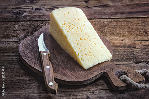 Fototapeta cheese and knife on a wooden board