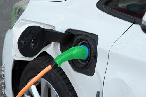 Ein Elektroauto wird an einer Ladestation geladen - 212532370