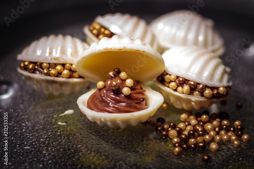 oyster-shaped candy made of chocolate, white chocolate (peel) and mini pearls of confectionery