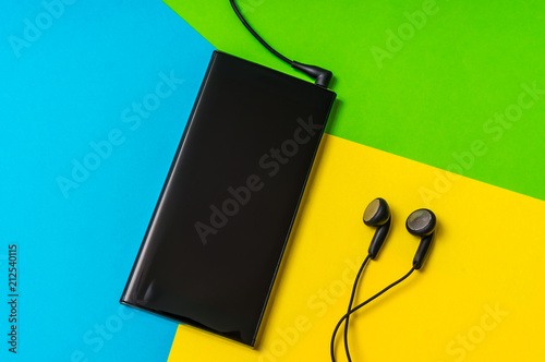 Mobile phone with headphones isolated on colorful background - 212540115