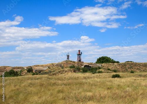 Fotobehang Vuurtoren lighthouse on the island on the hill, yellow grass