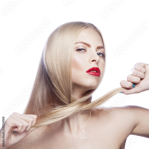 Leinwanddruck Bild Beauty young model girl hold hair in hands. Clean fresh perfect skin, red lips ,make-up. Blond hairstyle. White background. Isolated