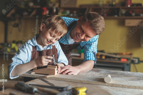 Smiling master and a little boy at work - 212545711