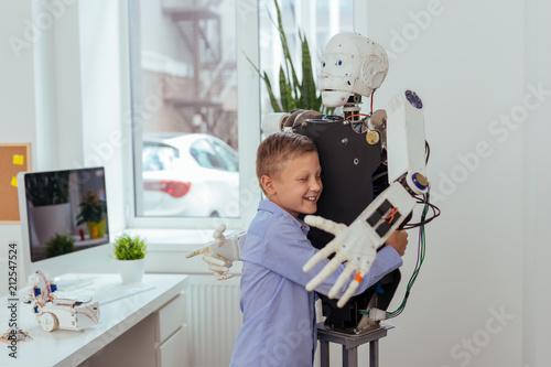Leinwanddruck Bild Best friend. Joyful happy boy smiling while hugging a robot