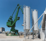 Exterior view of a cement factory with crane and concrete mixing silo - 212549747