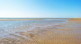Beach along the North Sea below a blue sky in sunlight in summer