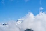 Wolken am blauen Himmel über Gebirge mit Schnee