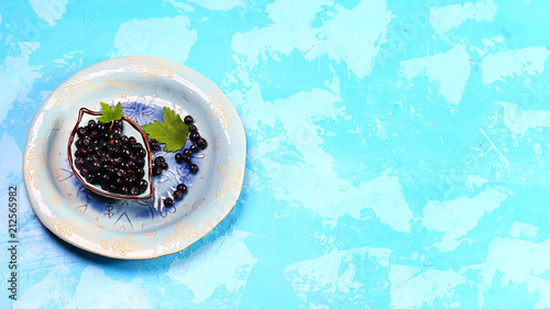 Superfood MAQUI BERRY. Superfoods antioxidant of indian mapuche, Chile. Bowl of fresh maqui berry and maqui berry tree branch on blue background, top view - 212565982