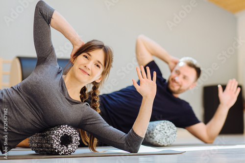Leinwanddruck Bild Gorgeous woman instructor performing back exercise on a foam roller at same time with handsome guy at pilates studio. Coach and patient doing fascia exercise on side surface of back.
