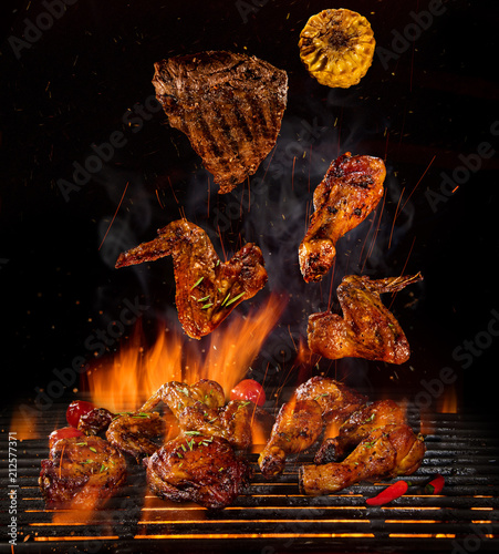 Wall mural Chicken legs and wings on the grill with flames