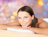 wellness and beauty concept - close up of beautiful woman at spa over holidays lights background
